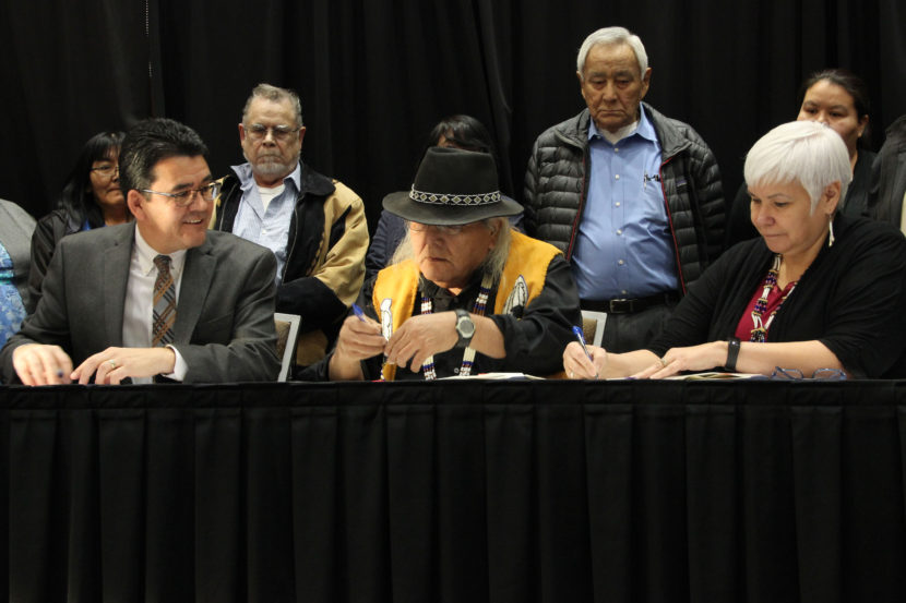 Deputy Interior Secretary Michael L. Connor joins Christopher Gene (center) and Karen Linnell of the Ahtna Intertribal Resource Commission to sign an agreement giving Alaska Native tribes in the Ahtna region more say over subsistence resources. (Photo by Rachel Waldholz, Alaska's Energy Desk - Anchorage)