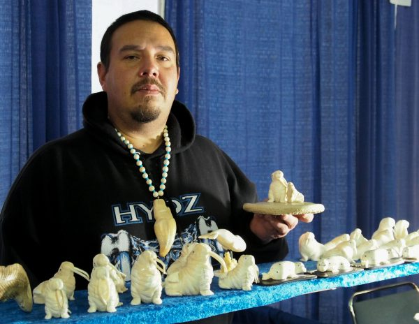 Dennis Pungowiyi shows off one of his favorite carving motifs, a mother walrus with her pup. (Photo: Zachariah Hughes, Alaska Public Media - Fairbanks)