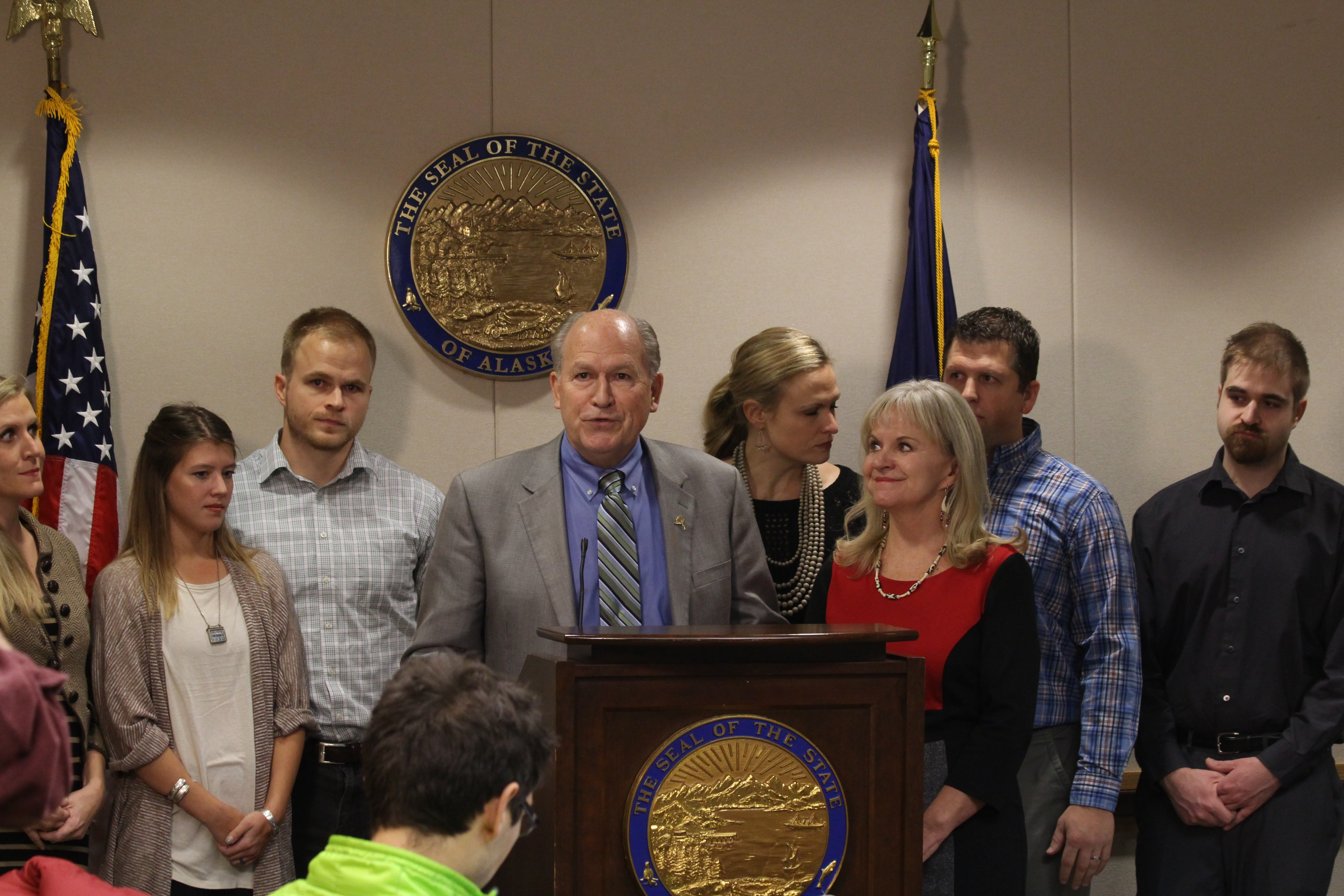 Bill Walker and (from left to right) Tessa Linderman (daughter), Sabrina Walker (daughter-in-law), Adam Walker (son), Lindsay Hobson (daughter), First Lady Donna Walker, Greg Hobson (son-in-law) and Jordan walker (son), as Governor Walker talks to press about his prostate cancer diagnosis. Not pictured: Lt. Governor Byron Mallott and Walker's brother Bob Walker. (Photo by Wesley Early, Alaska Public Media - Anchorage)
