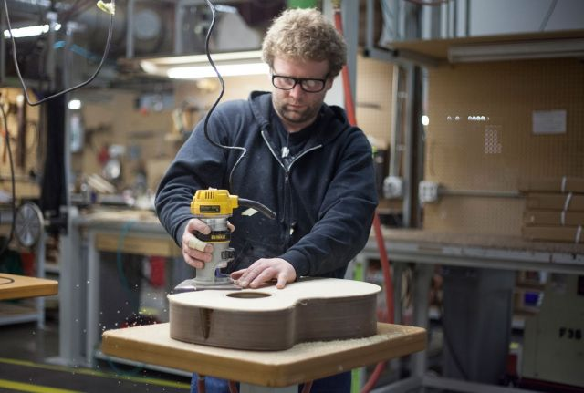 A worker routs the top of an acoustic guitar. (Photo by RA Beattie/Musicians for Forests)