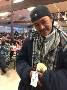 William Foster holds some of the ornaments he helped make at Bean's Cafe as part of a project funded by the Alaska Mental Health Trust Authority. (Hillman/Alaska Public Media)