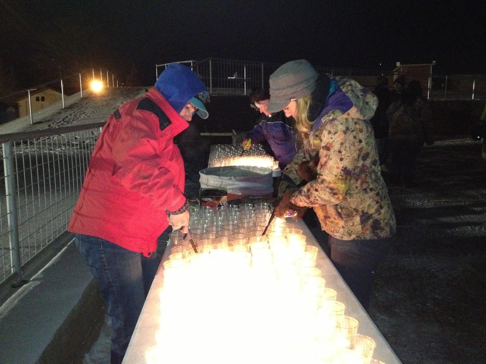 Azlyn Brandenburg and Catherine baher light votive candles before prayer vigil for David Grunwald on Friday. (Photo by Ellen Lockyer, Alaska Public Media - Anchorage)
