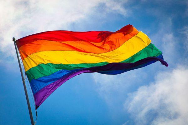 A rainbow flag wavees in a blue sky