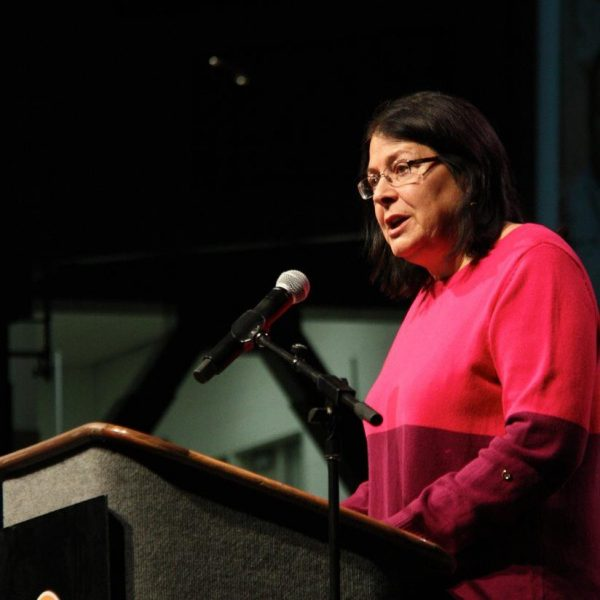 A woman in a pink shirt speaks at t