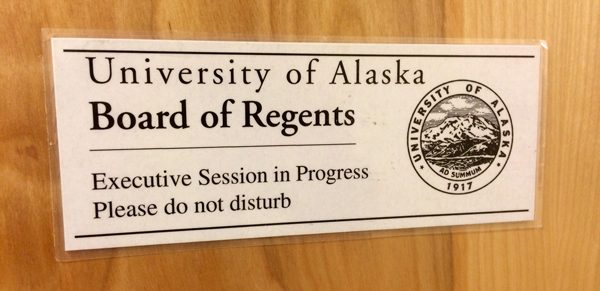 "A white sign on a light wooden door says  ""University of Alaska Board of Regents/Executive Session in Progress/Please do not disturb"""