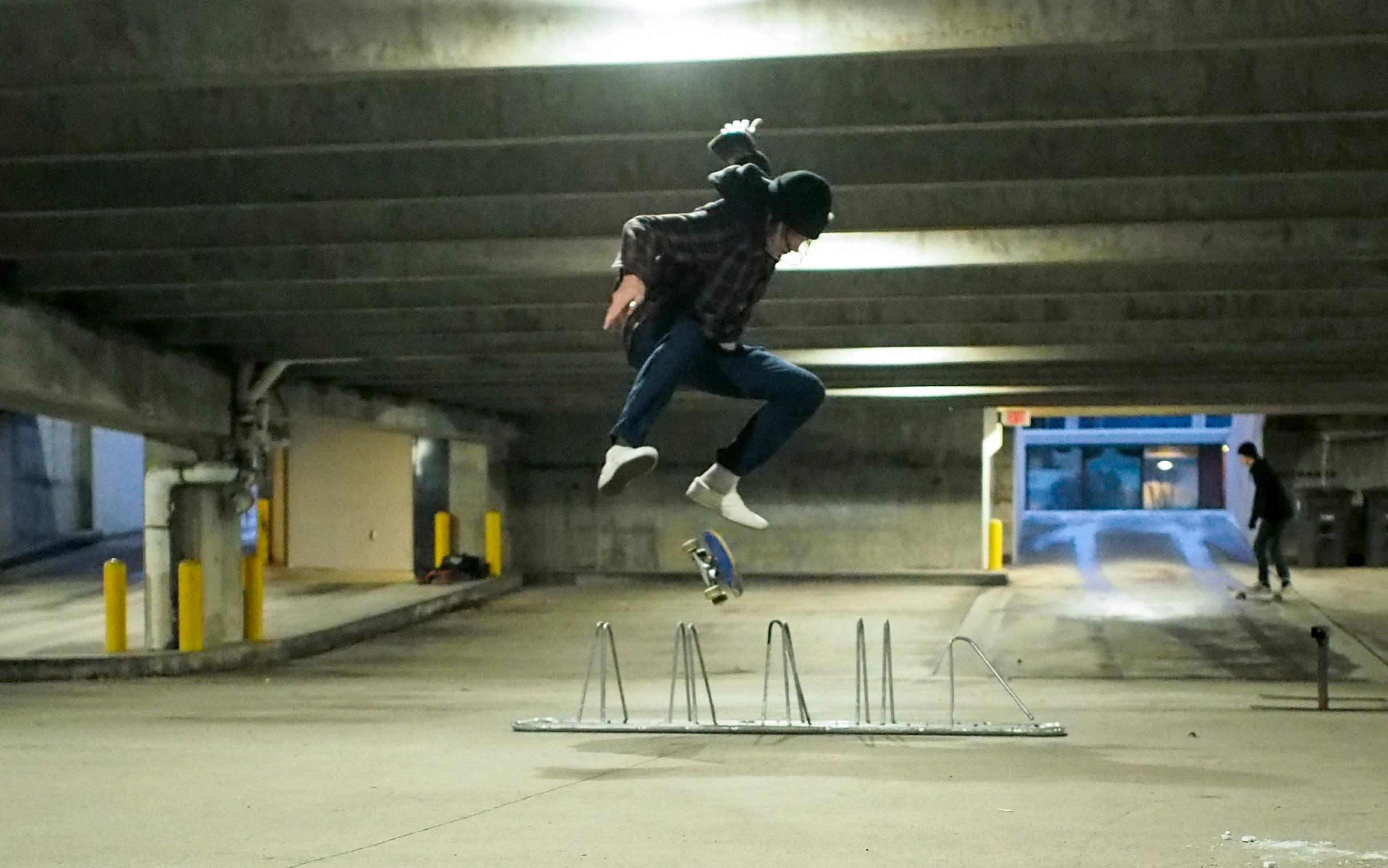 A Skateboarder Kickflips Over Bike Rack Inside Chilly Underground Parking Garage With Patches Of Ice And Snow On The Ground Photo Zachariah Hughes