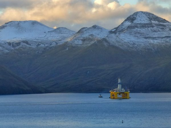 A yellow rig leaves a harbor under snow-covered mountains