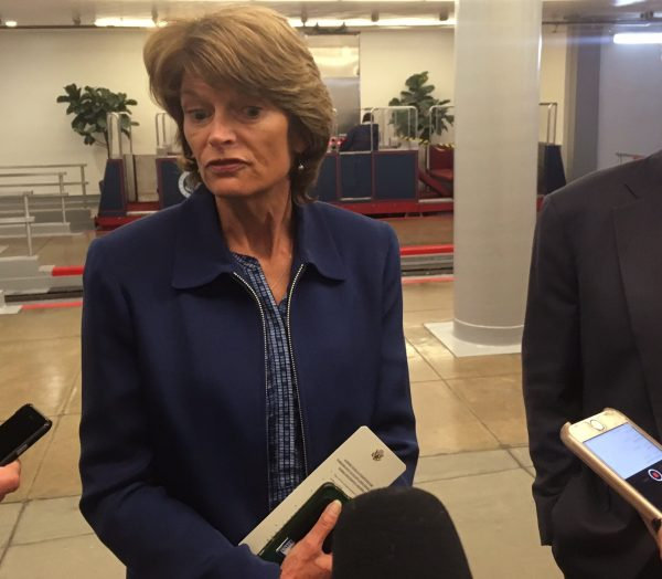 Sen. Lisa Murkowski with three recording devices in the foreground, held by people not in image.