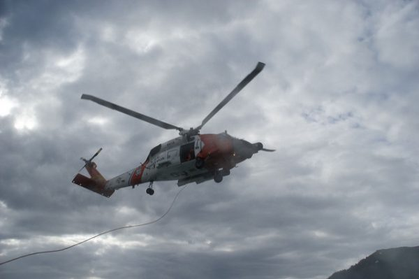 A white and grey coast guard helicopter over cloudy skies
