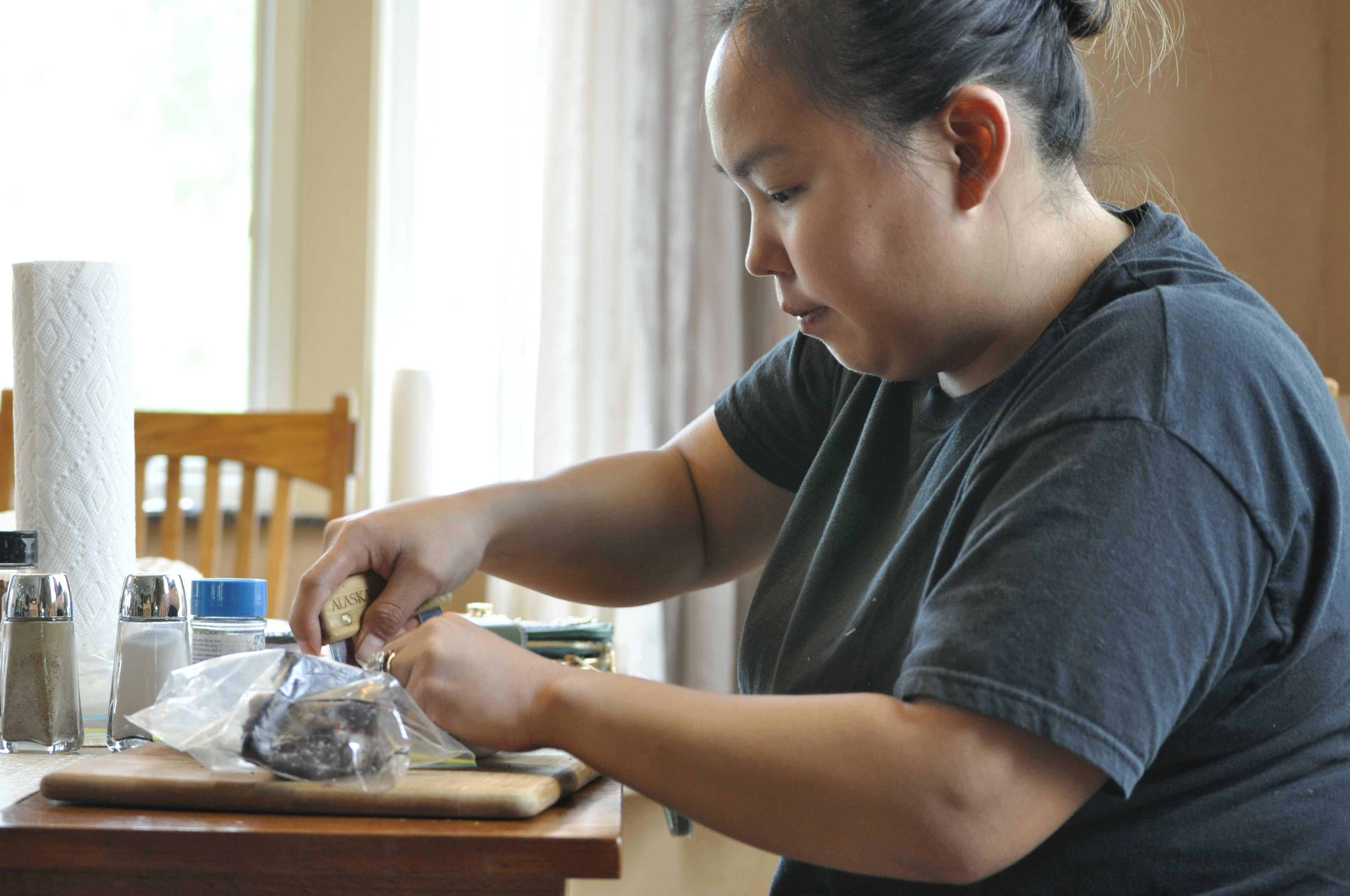 Alesha Tangman Uses An Ulu To Cut Up Pieces Of Bowhead Whale Meat At Her Aunt And Uncles Kitchen Table In Wasilla She Kunniaks Spice Mixtures On