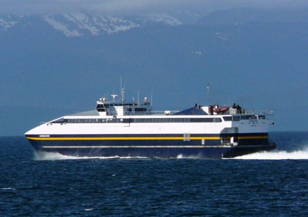 A blue and white ferry travels through the water on a clear day with mountains in the background