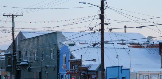 A snowy street neaer several bars