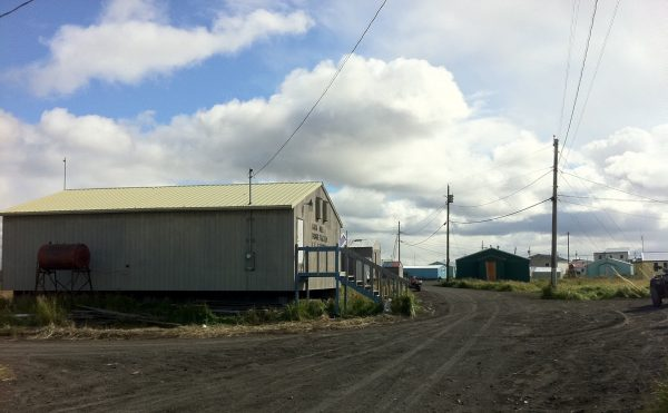 A grey building on a dirt road