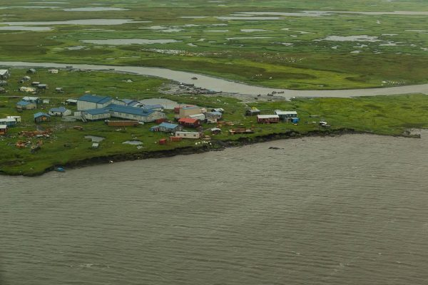 The Ninglik River shoreline is mere feet from houses in Newtok on July 26, 2019. As Newtok residents await relocation, the infrastructure erodes as quickly as the land. (Photo by Katie Basile, KYUK - Bethel)