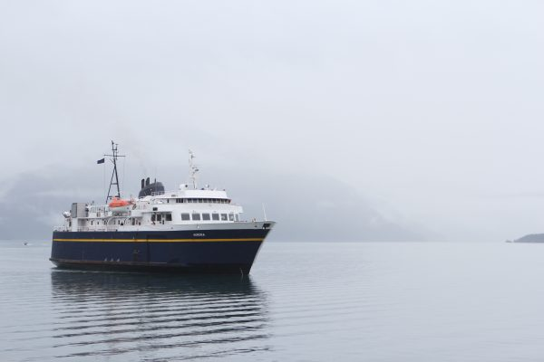 A blue and white ferry in the left hand side of the image sails in foggy weather and a foggy mountain in the background