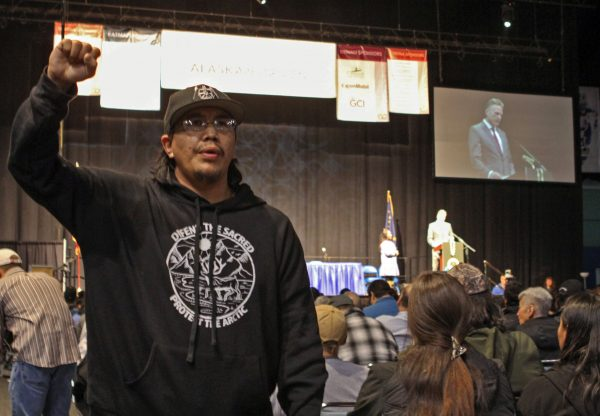 An Alaska Native man in a black sweatshirt stands and speaks