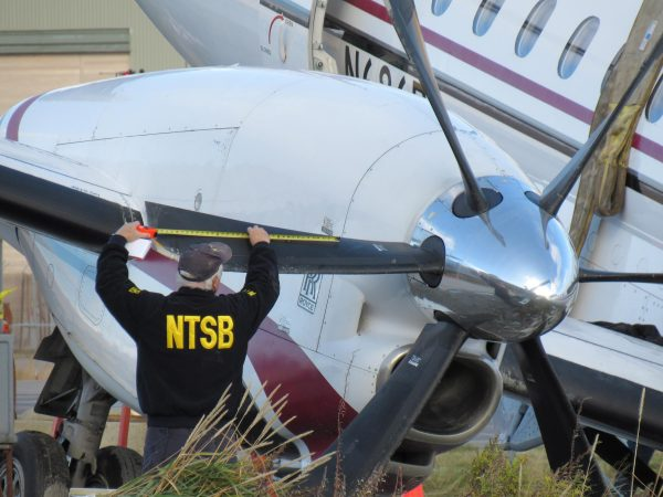 a man in a black uniform with the yellow letters NTSB holds a propellor of a crashed airplane