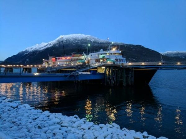 A ferry at a dock with a mountain in the background at twilight