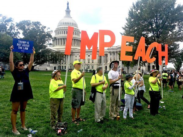 People stand with signs that spell impeach. white dome of capitol visible behind them