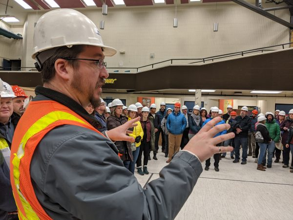 A structural engineer address the crowd on a tour of the damage at Gruening Middle School