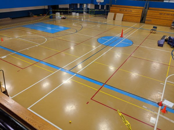 The Gruening Middle School gym floor. Traffic cones indicated where geotechnical engineers drilled through the floor into the soil to check for any geotechnical issues beneath the school