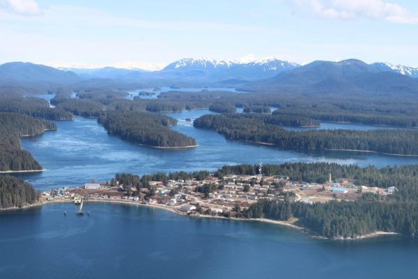 An aerial image of Angoon shows buildings on a small peninsula next to several other inlets.
