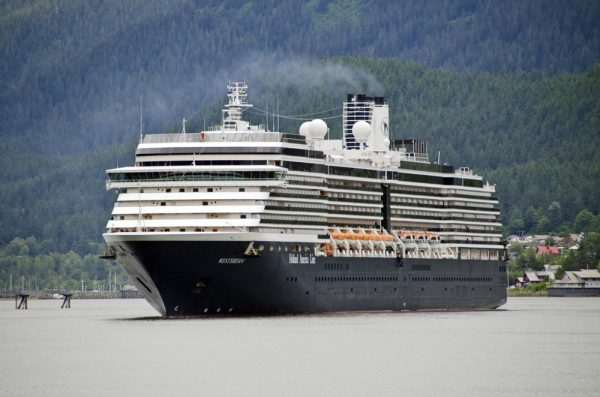 A large cruise ship with a white cabin and a blue hull