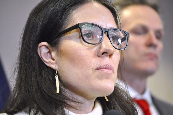 Close up shot of a woman with dark hair and eyeglasses looking into the distance
