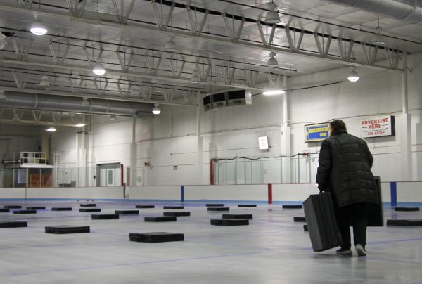 A worker lays out mats in an ice rink under bright flood lights.