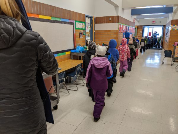 A line of elementary children line up and walk down the hallway out to recess in the winter