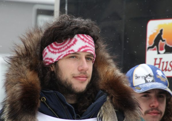 A man with a headband and winter jacket stares ahead.