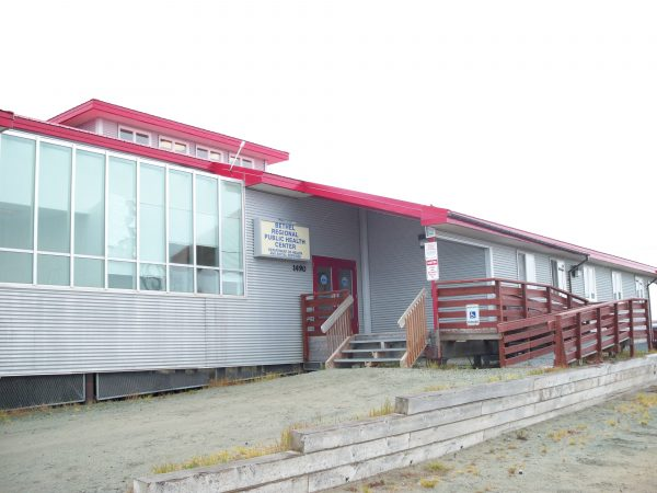 A grey building with a red roof and wooden stairs leading ip next to a boardwalk