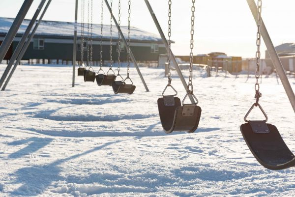 Empty swings in front of a school on a winter day