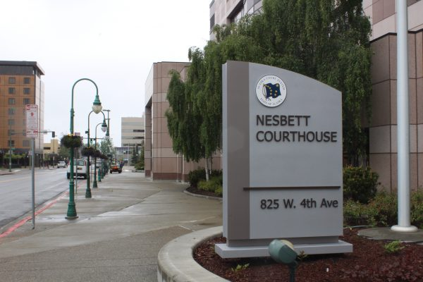 "A concrete sign with an emblem of the Alaska flag and the words ""Nesbett Courthouse"". A sidwalk and streetlamps are in the background"