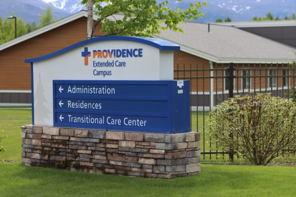 "A blue sign with directions that says ""Providence Extended Care"" and has a house in the background."