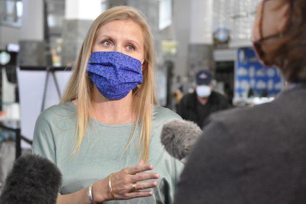 A white woman in blue maskspeks