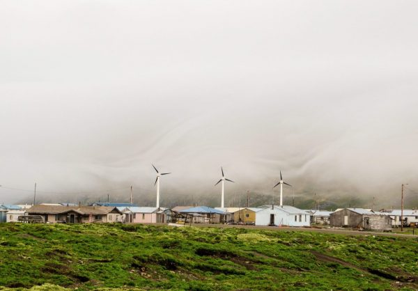 Three relatively small windmills turn above small, one-story homes. Green grass in the foreground and thick fog in the background .
