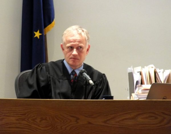 A white old man in a judge's robee sits at a desk in front of an Alaskan flag