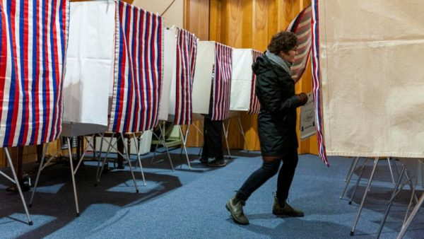 A voter enters a voting booth, with several other booths behind her.