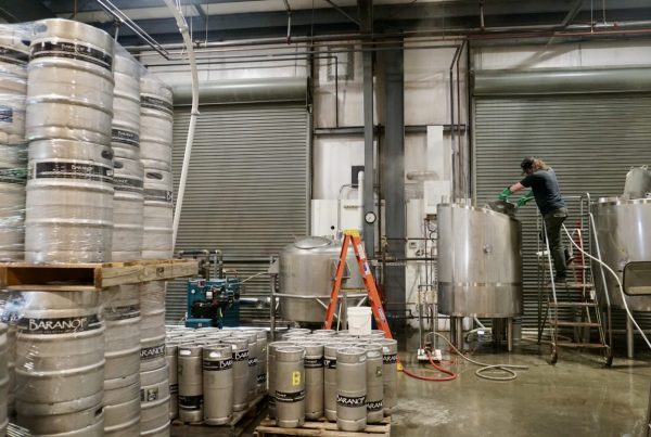 Stacks of silver canisters and kegss sit around a crowded warehouse along with ladders, tools, and a garage door in the back.