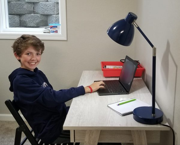 A young boy sits at a desk and smiles at the camera while working on a laptop