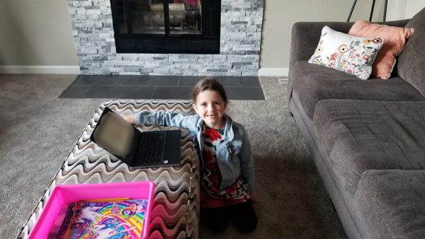 A young girl sits on the floor on of a living working on a laptop