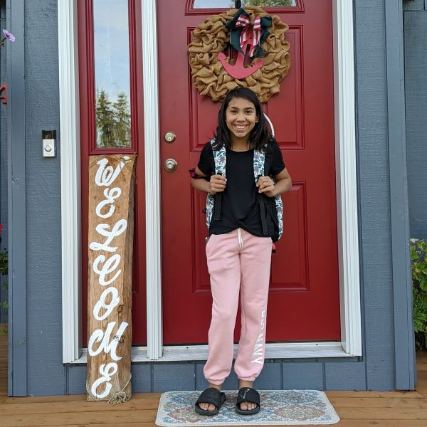 A young girl stands in front of a front door to a house smiling and wearing a back pack