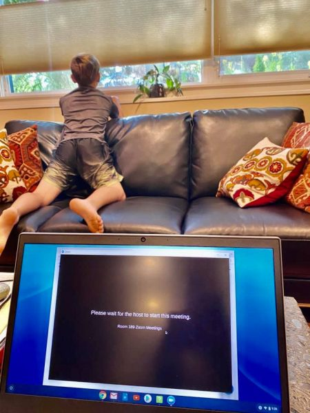 A young boy kneels on a couch and looks out the window as a laptop screen behind him shows a loading page