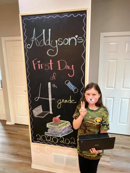 A young girl puts up the peace sign with one hand and holds a laptop in the other in front of a sign that says 'Addyson's first day of 4th grade'