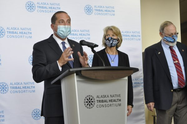 """A man in a suit stands at a podium that says on it """"alaska Native Tribal Health Consortium,"""" as does the backdrop. To the viewers right is Sen. Lisa Murkowski and Rep. Don Young. All three are wearing masks."""