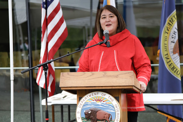 A woman in a red kuspuk (jacket) is standing at a podium that is affixed with the Interior Department seal.