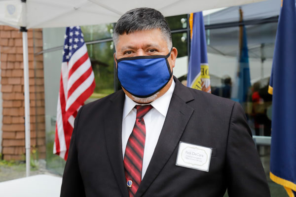 A big man in a suit an tie with a blue face mask stands in front of a U.S. flag with other flags in the background.
