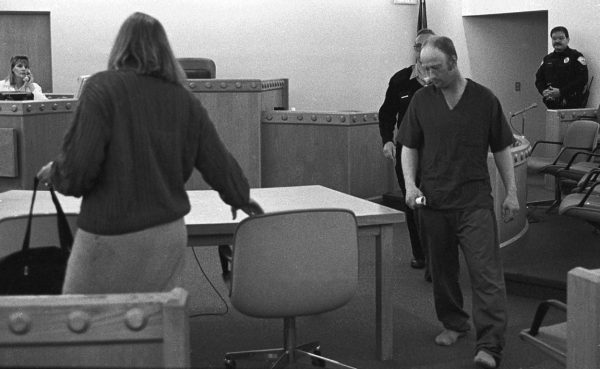 In a black and white photo, Richard Bingham walks towards a chair as a woman whose back is turned pulls ist out.