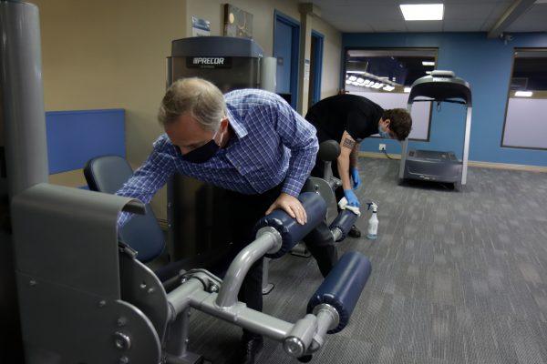 Alaska Club Chief Executive Robert Brewster helps sanitize a workout station at Alaska Club East.